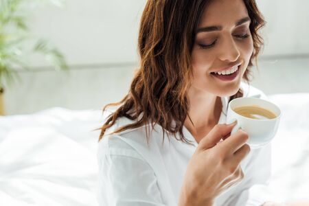 attractive woman in white shirt smiling and holding cup at morning