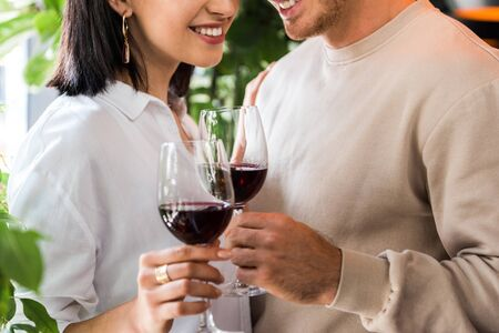 cropped view of happy man holding glass with red wine near cheerful girl Stock Photo