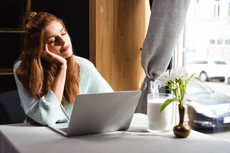redhead dreamy woman with closed eyes sitting in cafe with laptop Stock Photo