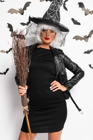 attractive woman in witch hat and wig holding broom in Halloween