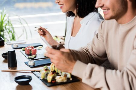 cropped view of young woman holding chopsticks near sushi and man in sushi bar