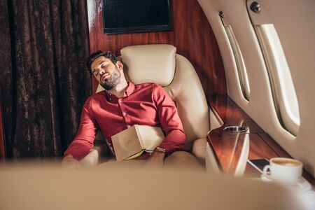 handsome man in shirt sleeping with book in private plane Stock Photo