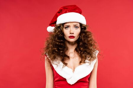 upset curly girl posing in santa costume, isolated on red