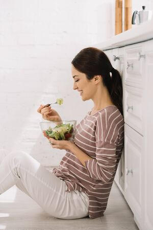 happy young woman sitting on floor in kitchen and eating vegetable salad Reklamní fotografie