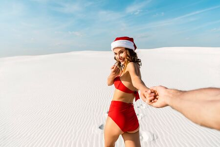 cropped view of boyfriend holding hand of sexy girlfriend in santa hat on beach in Maldives Reklamní fotografie