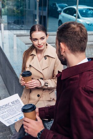 selective focus of attractive woman looking at man with newspaper and coffee to go