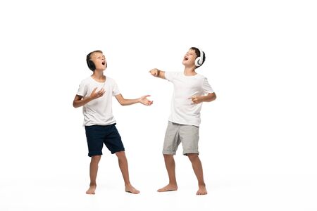 two excited brothers singing with closed eyes while listening music in headphones