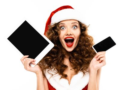 excited curly woman in santa costume holding digital devices with blank screens, isolated on white Reklamní fotografie