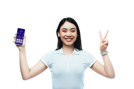 happy brunette asian woman holding smartphone with healthcare app and showing peace sign isolated on white