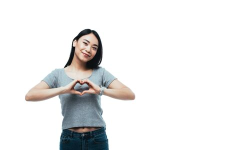 smiling attractive asian girl showing heart gesture isolated on white