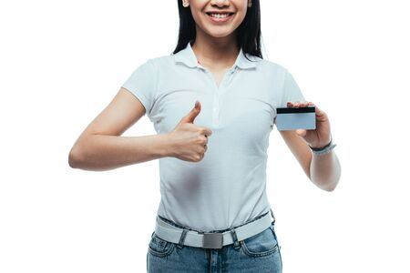 cropped view of happy attractive asian girl holding credit card and showing thumb up isolated on white Reklamní fotografie