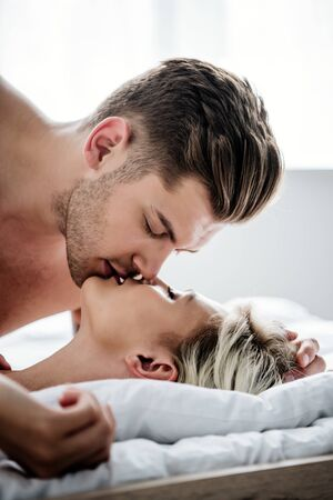 selective focus of handsome man kissing attractive woman in bed Reklamní fotografie
