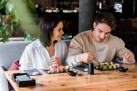 selective focus of happy man and woman near tasty sushi in restaurant