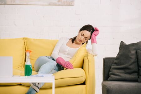 exhausted housewife sitting on yellow sofa with closed eyes near table with spray bottle Reklamní fotografie
