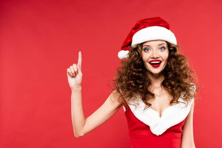 happy girl in santa costume pointing up, isolated on red