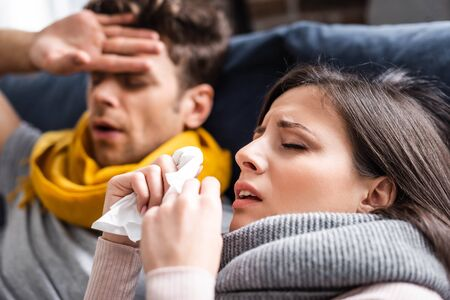 selective focus of sick girlfriend sneezing and holding napkin in apartment Reklamní fotografie