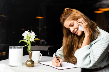 smiling girl talking on smartphone and writing in notepad in cafe and coffee cup