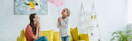 panoramic shot of cheerful babysitter looking at pink balloons near happy kid