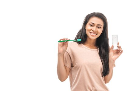 smiling african american woman holding toothbrush and toothpaste while looking at camera isolated on white