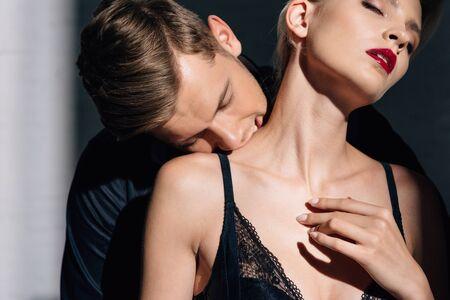 handsome man kissing woman in black underwear with closed eyes Reklamní fotografie