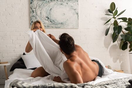 smiling young couple having fun and pillow battle in bed in the morning