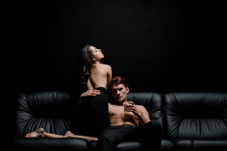 passionate woman and man with glass of whiskey posing on sofa in dark room