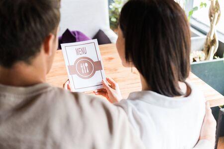 selective focus of young woman holding menu near man