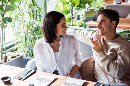 happy woman looking at man gesturing in sushi bar