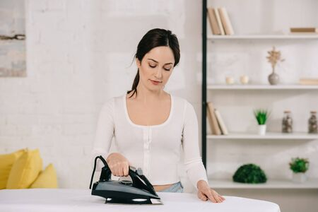 beautiful housewife smiling while ironing on ironing board