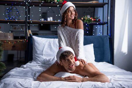 smiling girlfriend in santa hat sitting on boyfriend and hugging him at christmastime Reklamní fotografie