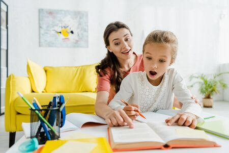 selective focus of happy babysitter pointing with finger at book near surprised kid