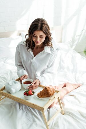 attractive woman in white shirt having breakfast in bed at morning