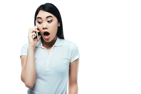 surprised attractive asian girl with open mouth talking on smartphone isolated on white Reklamní fotografie