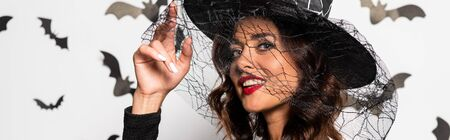 panoramic shot of attractive woman in witch hat looking at camera in Halloween Reklamní fotografie