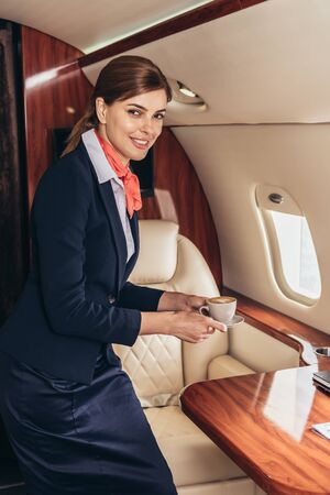 smiling flight attendant in uniform looking at camera and holding cup in private plane
