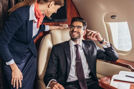 smiling businessman in suit looking at flight attendant in private plane Stockfoto