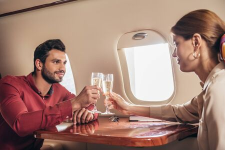 boyfriend and girlfriend clinking with champagne glasses in private plane