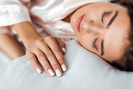selective focus of attractive woman sleeping in bed at morning