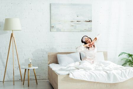 attractive woman in sleeping mask stretching herself at morning Reklamní fotografie