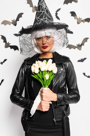 attractive woman in witch hat and wig holding bouquet in Halloween Reklamní fotografie