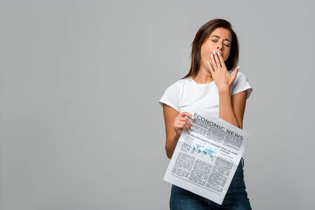 bored young woman yawning and holding economic newspaper, isolated on grey