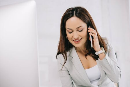 smiling young secretary talking on smartphone while standing at workplace in office Reklamní fotografie