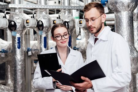 engineers in white coats looking at folder near compressed air system Reklamní fotografie