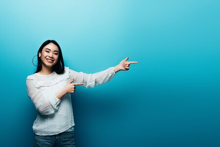 smiling brunette asian woman pointing with fingers on blue background Reklamní fotografie