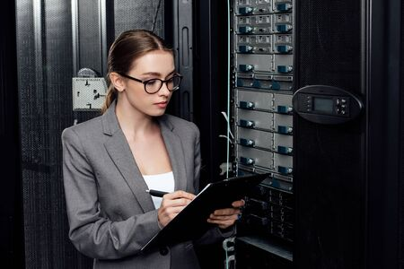 businesswoman in glasses holding clipboard while writing in data center