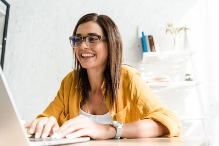 beautiful smiling freelancer working with laptop in home office