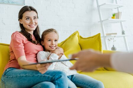 happy babysitter sitting near happy kid and mother with clipboard