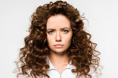 attractive upset curly girl in white t-shirt, isolated on white