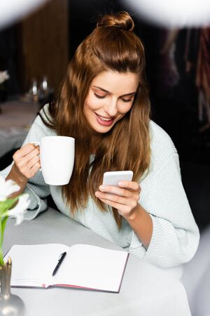 happy woman with cup of coffee using smartphone in cafe with notepad