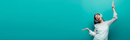 smiling asian woman with closed eyes in headphones holding smartphone and dancing on turquoise background, panoramic shot